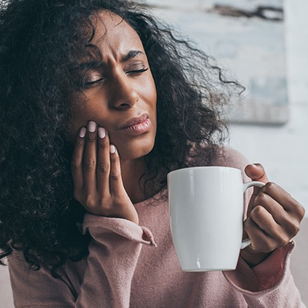 person in need of tooth extraction holding their mouth in pain while drinking a cup of coffee