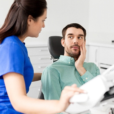 A male patient touching his cheek while talking to the dentist