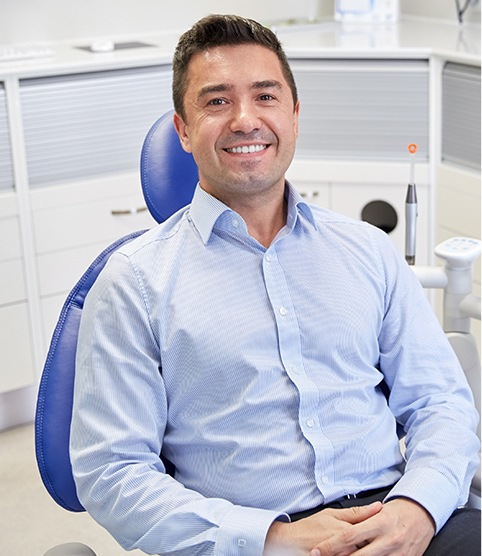 Smiling man in dental chair for preventive dentistry