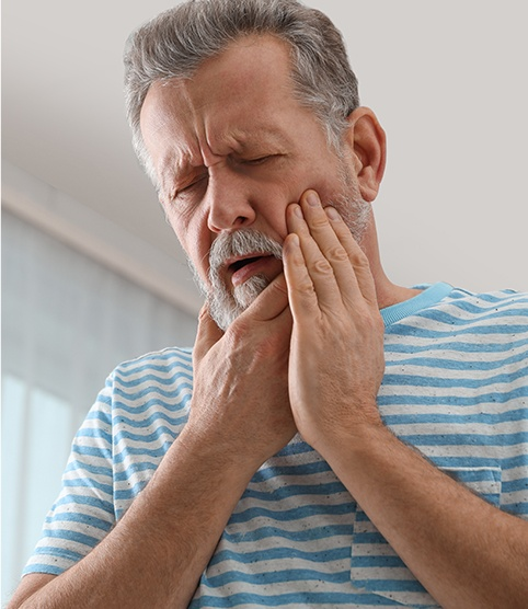 Older man in pain holding jaw before emergency dentistry