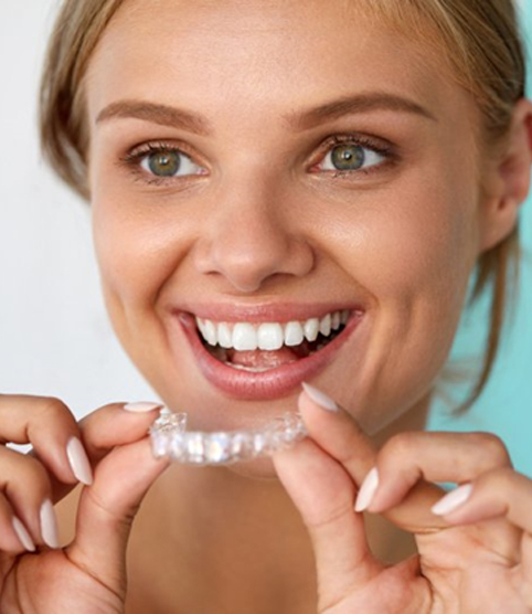 A woman smiling and holding an Invisalign clear aligner